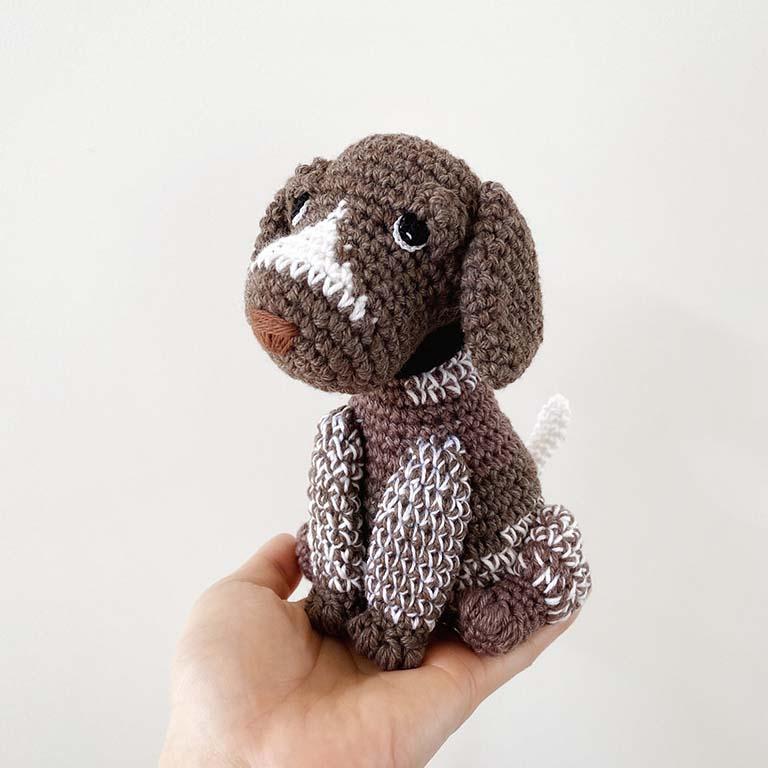 Hand holding crochet dog toy